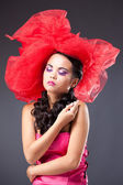 Beautiful brunette woman in red tulle hat looking at camera — Stock Photo