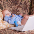 Royalty-Free Stock Photo: Serious businessman baby sits with the computer on sofa