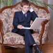 Young confident boy dressed in business suit sitting with comput - Foto Stock