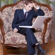 Worried young boy dressed in business suit working on computer — Stock Photo