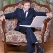Young smiling boy dressed in business suite looking at white not — Stock Photo #5010702