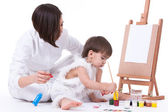 Happy mom and son dressed in white painting near easel — Stock Photo