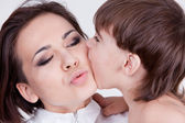 Closeup portrait of kid bitting his kissing mother on cheek — Stock Photo