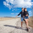Fashion couple try to stop the car on old road — Stock Photo
