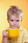 Funny little boy drink from big yellow cup — Stock Photo