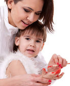 Happy mother painting her son's hands near easel — Stock Photo