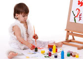 Cute sitting baby in white painting with brush near easel — Stock Photo