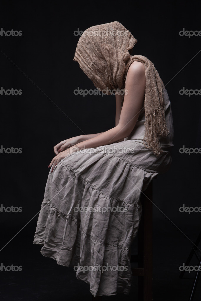Conceptual portrait of a sad woman in scarf sitting with hidden face and lowered head — Stock Photo #5175980