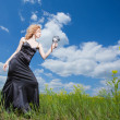 Beautiful pashionate woman on field filming with old camera — Stock Photo #5185305