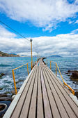 Long wooden footbridge over the ocean — Stock Photo