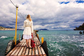Donna con ombrello e borsa a mani, camminando sul mare in legno footb — Foto Stock
