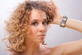 Beautiful young blonde curly woman holding hair with hands — Stock Photo
