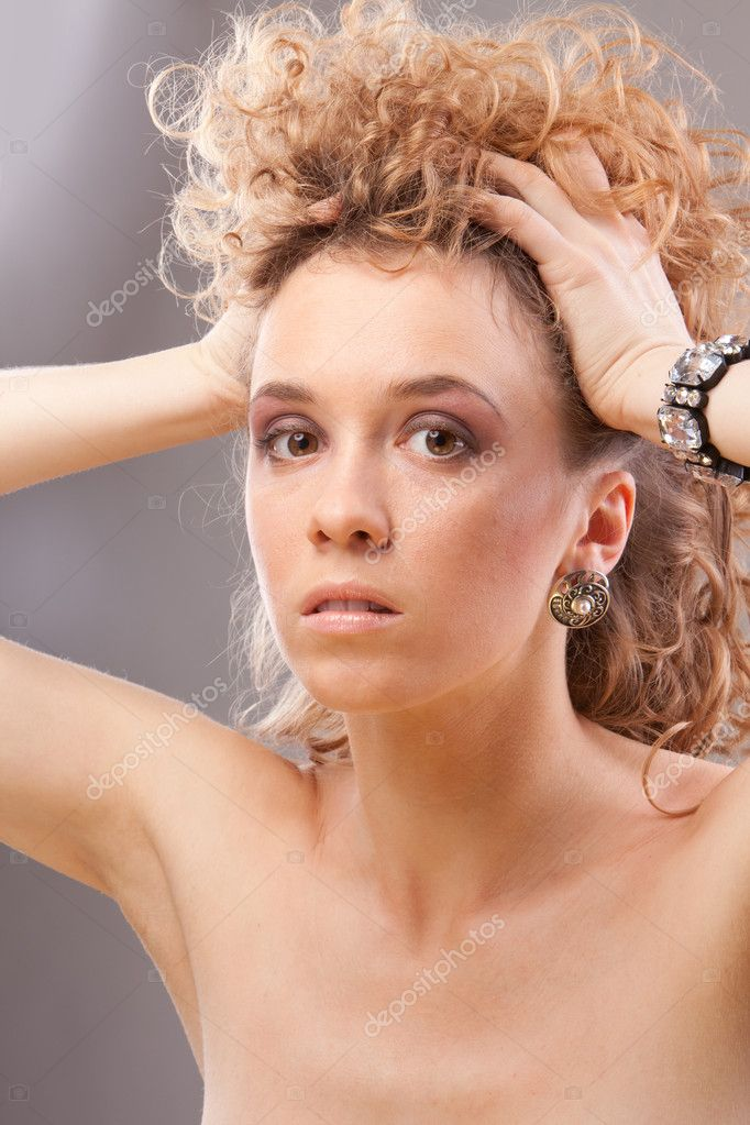 Beautiful young blonde curly woman holding head with hands looking at camera — Stock Photo #5185333