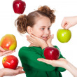 Surprised smiling girl choosing among proposed apples — Stock Photo #5194618