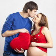 Royalty-Free Stock Photo: Man kissing his pregnant wife nose holding red heart