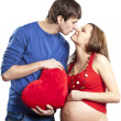 Happy joking couple embracing pregnant belly and red heart — Stok fotoğraf