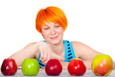 Smiling red hair woman choosing apple — Stock Photo