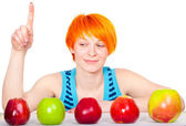 Smiling cute red hair woman choosing apple — Stock Photo