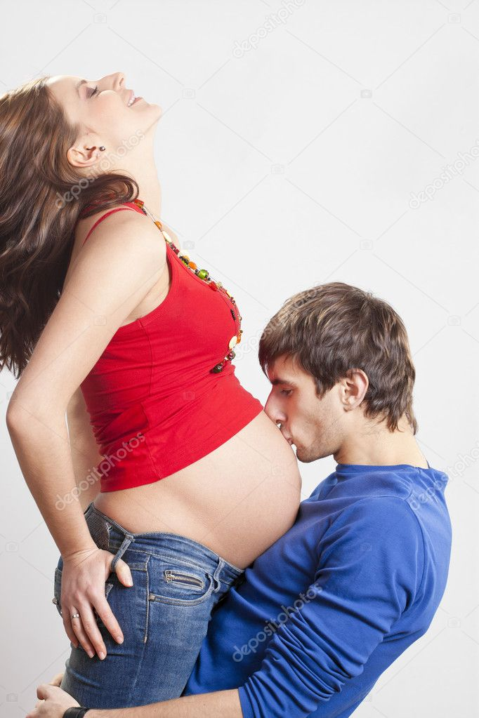 Portrait of man kissing his pregnant smiling wife at belly — Stockfoto #5201625
