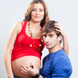 Man showing ok sign on his wife's pregnant belly — Stock Photo
