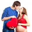 Happy joking couple embracing pregnant belly and red heart - Stock Photo