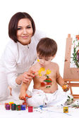 Joking mother in white painting her son's hands — Stock Photo