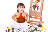 Funny child spreading paints with hands on stomach — Stock Photo