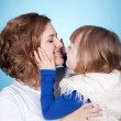 Smiling child and mom embracing — Stock Photo