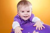 Happy little boy laughs near violet ball — Stock Photo
