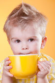 Funny boy drink from yellow cup — Stock Photo