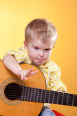 Funny boy with guitar showing peace sign and tongue — Stock Photo