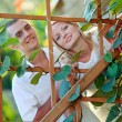 Young happy couple at wooden lattice - Stock Photo
