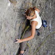 Female rock climber clinging to a cliff as she battles her way up — Stock Photo