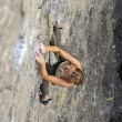 Female rock climber clinging to a cliff as she battles her way up - Stock Photo