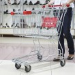 Lower half waist down image of woman in jeans pushing a shopping cart in a shoe store — Stock Photo