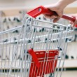Woman pushing shopping cart in shoe store, close-up — Stock Photo