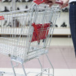 Woman pushing shopping cart in shoe store, close-up - Stock Photo