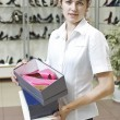 Royalty-Free Stock Photo: Young attractive shop assistant holding a couple of shoe boxes on the background of shoe department