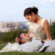 Stock Photo: Happy wedding couple lying on grass in park