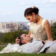 Happy wedding couple lying on the grass in the park — Stock Photo