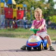 Stock Photo: Preschooler driving his toy vehicle in park