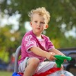 Little boy driving his toy vehicle in the park — Stock Photo