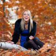 Young woman sitting on tree against autumn leaves — Stock Photo