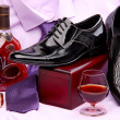 Set of male shoes, bottle and glass of brandy, and male wristwatch placed on a violet shirt with a tie — Foto de Stock