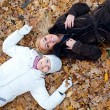 Two female friends lying down in autumn leaves — Stock Photo