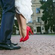 Stock Photo: Groom lifting his bride up during their walk, close-up of lower part of bodies