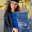 Stock Photo: Young female graduate with stack of boxes