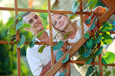Young happy couple at wooden lattice — Stock Photo