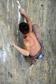 Male rock climber clings to an overhanging rock — Stock Photo