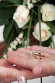 Wedding rings in hand on the background of bridal bouquet — Stock Photo